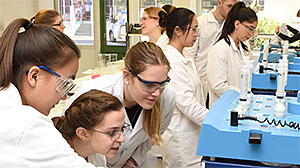 Group of young scientists in front of a laboratory equippment