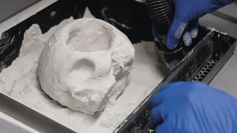 The model of the skull with a hole in one side is created using a 3D powder printer in a technique that makes do without supporting structures. (Bild: Universität Basel, Christian Flierl)