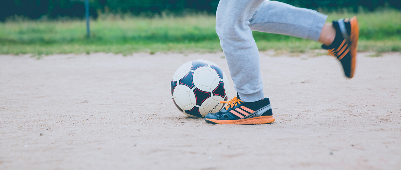 Shot of the legs of a kid playing soccer