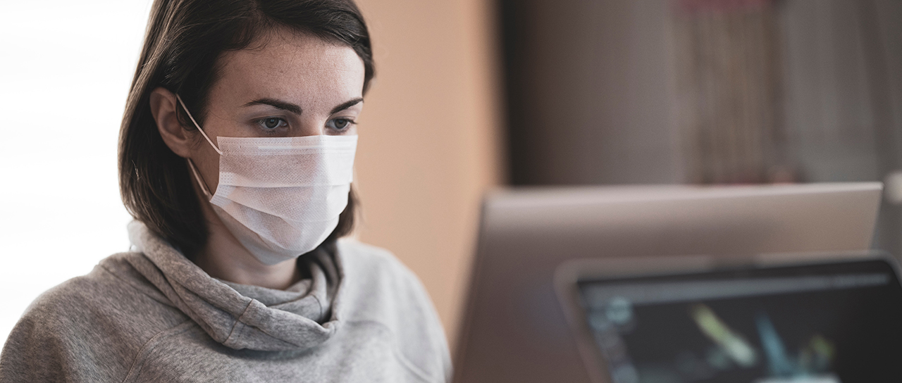 Woman with face mask at a computer