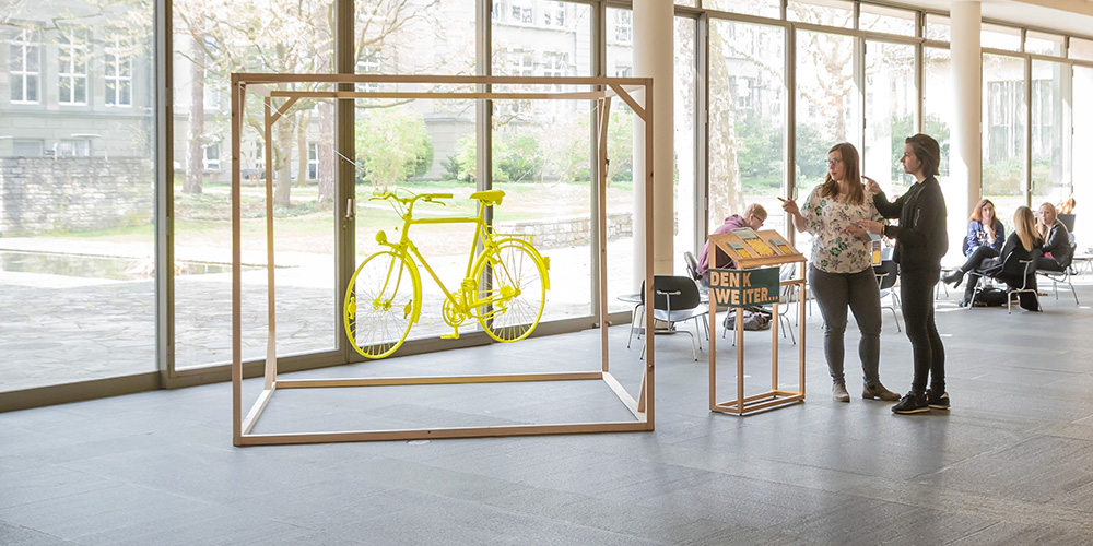 Installation during the Sustainability Week Basel showing a yellow bike hanging in a cubus