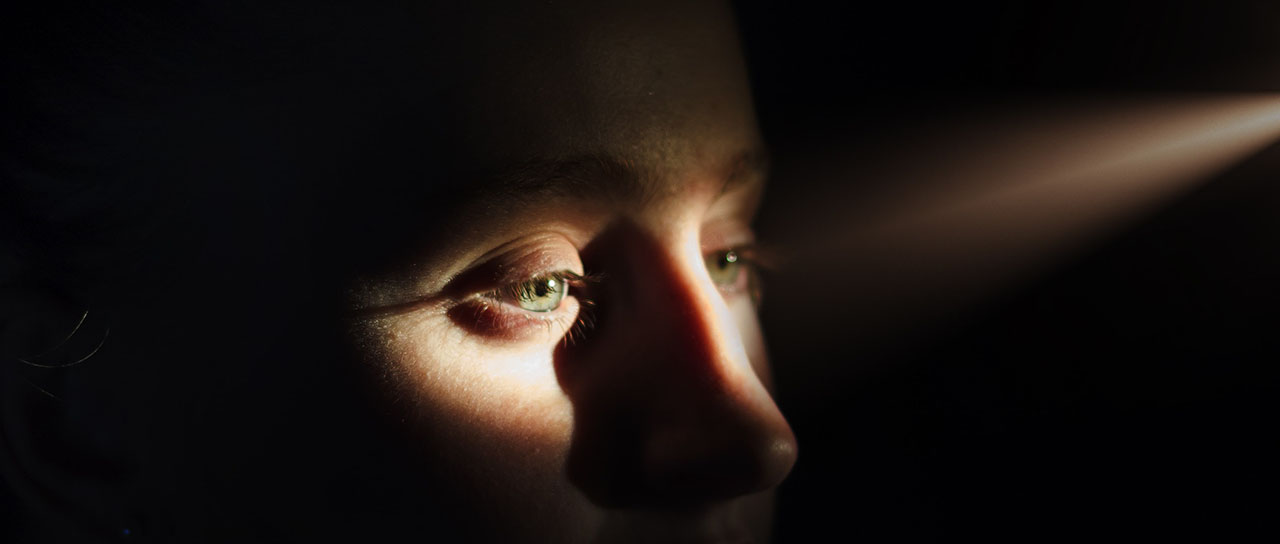 Face of a woman in the dark with a spot of light hitting her eyes