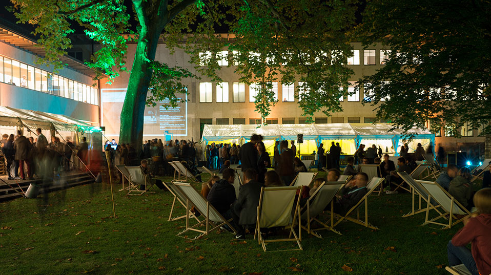 Guests at the University Fest in the garden of the collegiate building at night